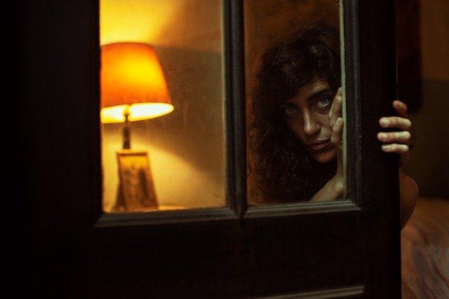 žena za prosklenými plastovými dveřmi